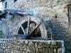 Un primo piano della ruota idraulica: si distinguono i cassetti e la parte finale della roggia, chiamata doccia.vedono