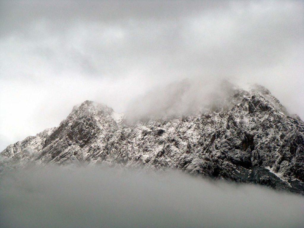 Il Crissin avvolto tra le nubi dopo una leggera nevicata; sulla destra appare la cima dello Schiavon sulla cui sommità si intuisce la croce di vetta